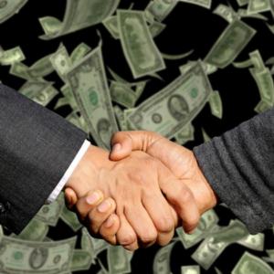 Mani che si stringono con sfondo di denaro